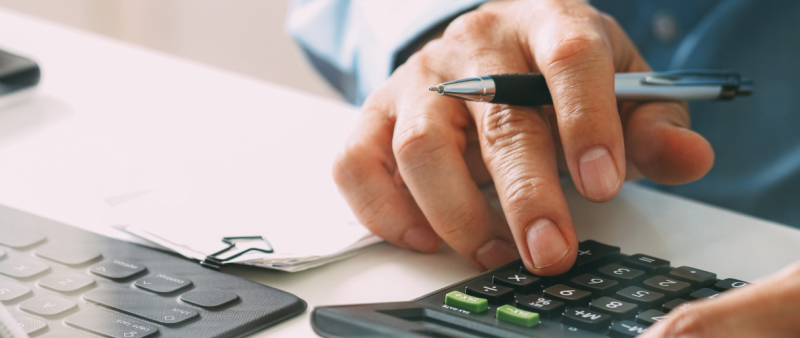 Business person using a calculator and keyboard
