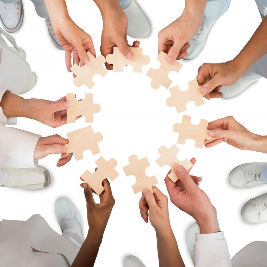 Circle of medical professionals each holding a piece of a puzzle
